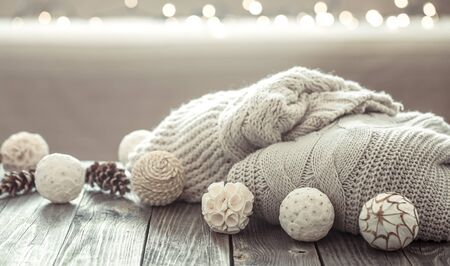 Cozy Christmas background on a wooden background with Christmas decorations and knitted sweater in a homely atmosphere.