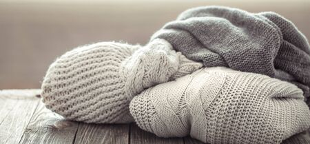A cozy stack of knitted sweaters on a wooden background . Close up. Reklamní fotografie