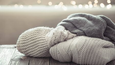 A cozy stack of knitted sweaters on a wooden background . Close up. Banque d'images