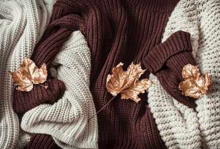 Hello Autumn flat lay background. Autumn background with cozy sweaters and gold leaves. Top view.