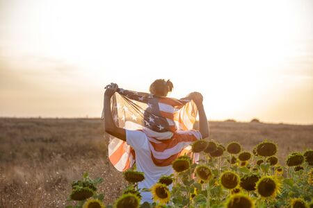 Happy family, dad and daughter holding the American flag at sunset. Dressed in white. The concept of family values and friendship . Patriotic feeling. Banco de Imagens
