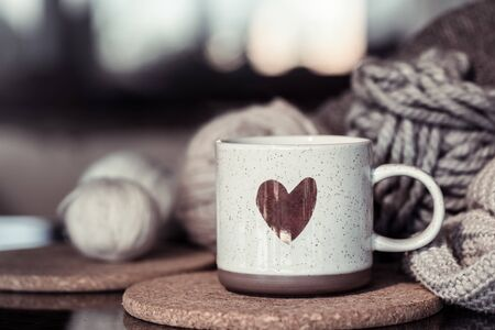 Cozy Autumn still life background with a beautiful Cup with a heart . Close up.