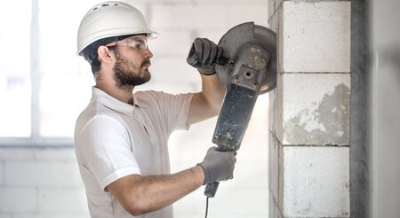 The industrial Builder works with a professional angle grinder to cut bricks and build interior walls. Professional on the construction site. The concept of electrician and handyman.