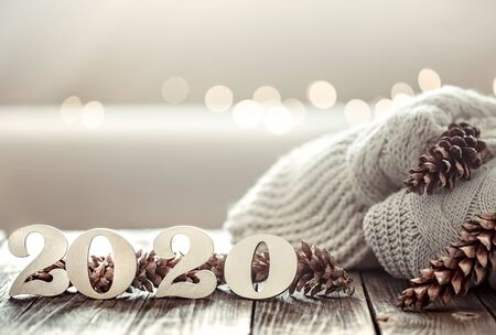 Cozy new year background new year 2020 on a wooden background with cones and knitted sweater in a homely atmosphere.