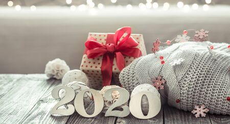 Cozy new year background new year 2020 on a wooden background with a gift with a red ribbon and Christmas decor items in a homely atmosphere.