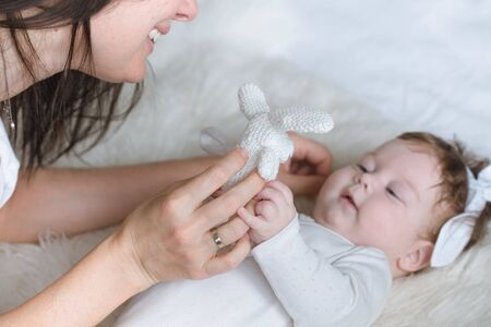 Mom plays with a toy with her newborn daughter, lying on the bed, top view. The concept of motherhood and child development. Stock Photo