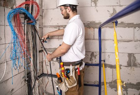 Electrician working near the Board with wires. Installation and connection of electrics. Professional with tools in hand. Фото со стока
