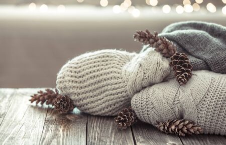 A cozy stack of knitted sweaters on a wooden background with beautiful bumps and lights in the background.