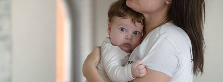 portrait of mom with cute little newborn girl. The concept of motherhood and family. Stock Photo