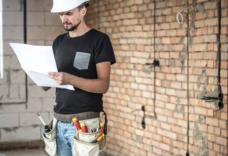 Builder handyman with construction tools, looking at the drawings on the construction site. House and house renovation concept background.