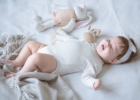 Portrait of newborn cute girl with soft toys lying on bed, top view. The concept of motherhood and child development.