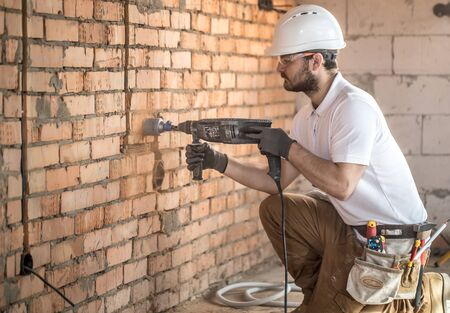 Handyman uses jackhammer, for installation, professional worker on the construction site. The concept of electrician and handyman. House and house reconstruction. Stok Fotoğraf
