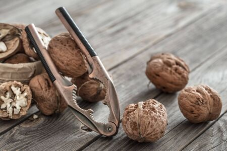 An organic nut lies in a box with a Nutcracker on a wooden background, close-up . The concept of healthy eating. Natural Walnuts . Banque d'images