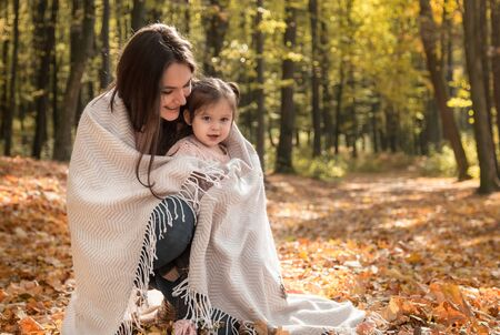 Mother and daughter in the autumn cozy forest covered with a blanket . The concept of family relations and children. Reklamní fotografie