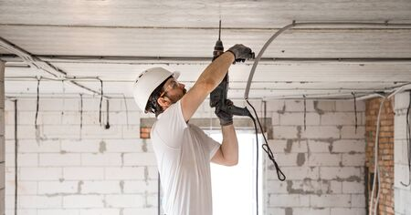 Handyman uses jackhammer, for installation, professional worker on the construction site. The concept of electrician and handyman. House and house reconstruction. 写真素材