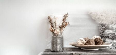 Still life decor details in the living room, a beautiful vase with dried flowers . The concept of comfort and home decor.