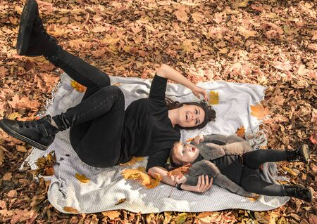 Mother and daughter play on a blanket in the autumn forest. The concept of family relations and children. The view from the top.