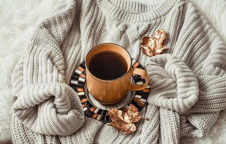 Still life with gold leaves and a yellow large Cup of tea wrapped snugly in a sweater . The concept of the autumn mood . Top view.