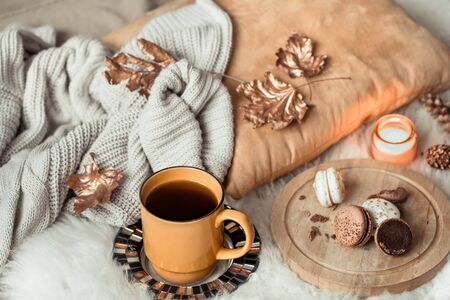 Still life yellow large Cup of tea and dessert macaroon, in the autumn interior with autumn leaves and a cozy sweater . The concept of the autumn mood .