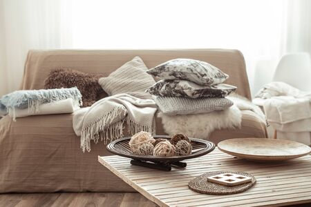 Modern interior of the living room with a sofa and decorative items on the table . Decorative pillows and blankets. Coziness and comfort at home . Stock fotó