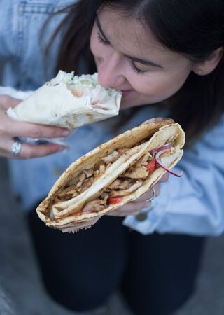 A young woman holding fast food. Close up. The view from the top. The concept of fast food . Stok Fotoğraf