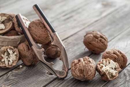 An organic nut lies in a box with a Nutcracker on a wooden background, close-up . The concept of healthy eating. Natural Walnuts . 写真素材 - 132049731