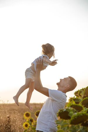 Happy family, dad with a little daughter playing in the field at sunset. The concept of family values and friendship.