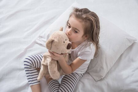 Cute little girl in white bed playing with soft bear toy . Concept of sleep and development of children .