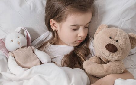 Cute little girl in a white bed sleeping with a soft toy . The concept of children's sleep and development .