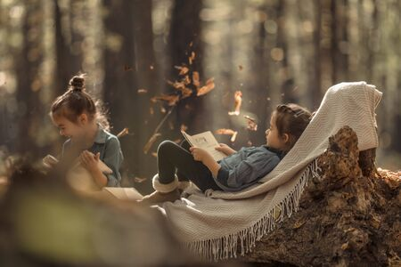two beautiful little girls reading books in the autumn forest , sitting on a log. The concept of education and friendship. Reklamní fotografie - 132224892