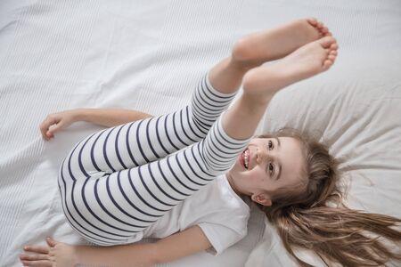 Linda niña divertida con el pelo largo en la cama se despertó por la mañana. Concepto de sueño y desarrollo de los niños.