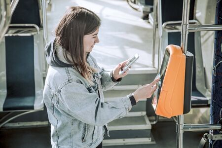 A young woman contactless pays for public transport. Payment by card, Bank transfer .