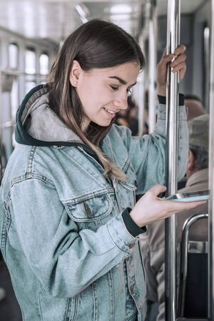 Young woman with phone in public transport. Urban style.