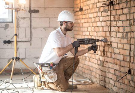 Handyman utiliza martillo neumático, para la instalación, trabajador profesional en el sitio de construcción. El concepto de electricista y personal de mantenimiento. Reconstrucción de casas y casas.
