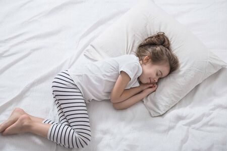 Cute little girl with long hair sleeping in a white bed. The concept of sleep and child development. the view from the top.