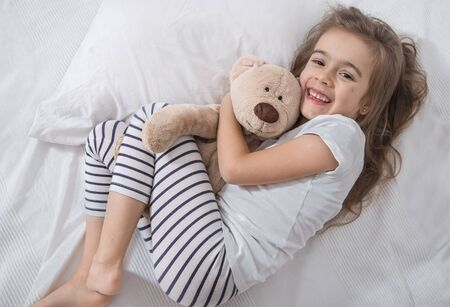 Cute little girl in white bed playing with soft bear toy . Concept of sleep and development of children . Banque d'images