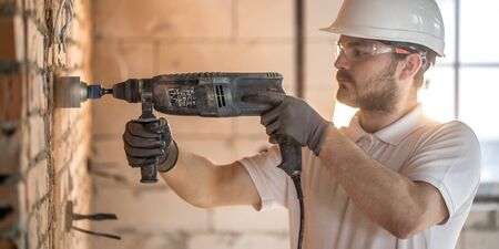 Handyman uses jackhammer, for installation, professional worker on the construction site. The concept of electrician and handyman. House and house reconstruction. 版權商用圖片
