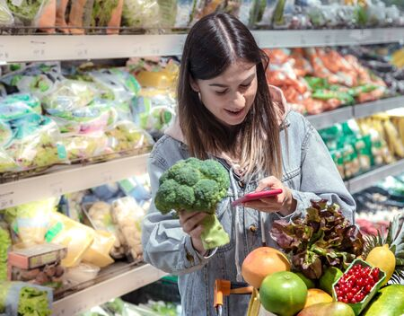 A young woman buys groceries in a supermarket with a phone in her hands. Health food. Reklamní fotografie