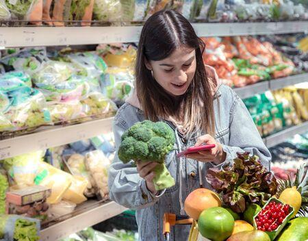 Eine junge Frau kauft mit einem Telefon in der Hand Lebensmittel in einem Supermarkt. Gesundes Essen. Standard-Bild