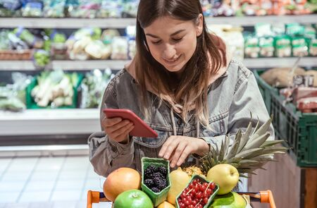 A young woman buys groceries in a supermarket with a phone in her hands. Health food.