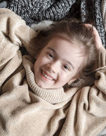 Portrait of an adorable toddler girl wearing fashion knitted clothes. Lies on backdrop of of multiple different cozy knitted sweaters. The concept of warm clothes.