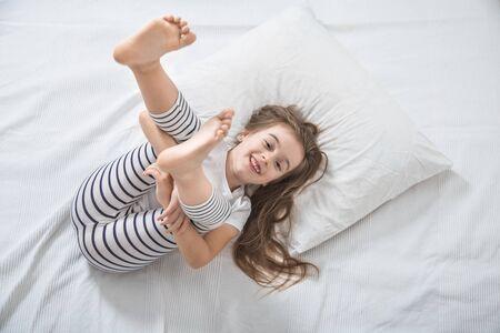 La ragazza carina e divertente con i capelli lunghi a letto si è svegliata la mattina. Concetto di sonno e sviluppo dei bambini.