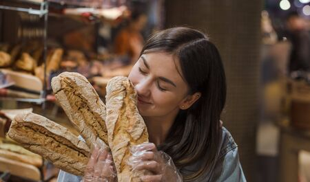 Only the best and fresh bakery. Young woman in supermarket with fresh bread . Health food. Healthy food, organic products.