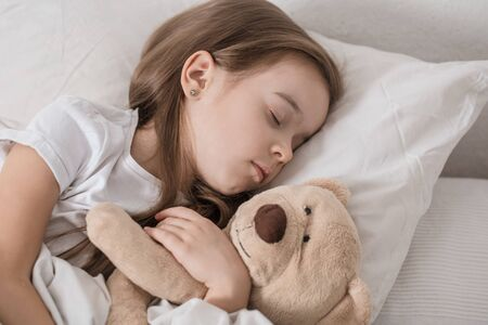 Cute little girl in a white bed sleeping with a soft toy . The concept of childrens sleep and development .