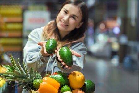A young woman buys groceries in a supermarket. Health food. Healthy food, organic food. Stock Photo