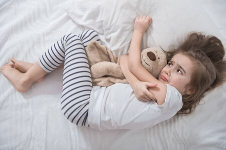 Cute little girl in white bed, sad hugging soft bear toy . Concept of sleep and development of children .