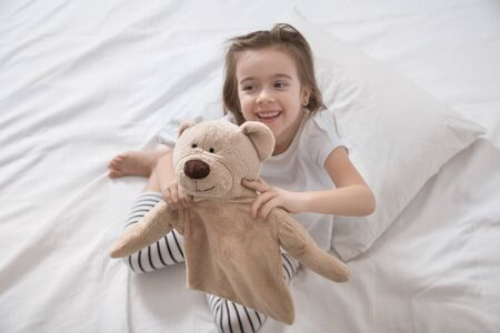 Cute little girl in white bed playing with soft bear toy . Concept of sleep and development of children . 写真素材