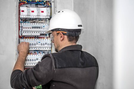 an electrical technician working in a switchboard with fuses. Installation and connection of electrical equipment. Professional with tools in hand.