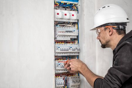 an electrical technician working in a switchboard with fuses. Installation and connection of electrical equipment. Professional with tools in hand. concept of complex work, space for text.