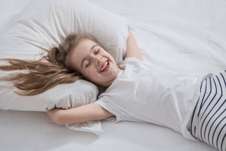 Cute little fun girl with long hair in bed woke up in the morning . Concept of sleep and development of children.